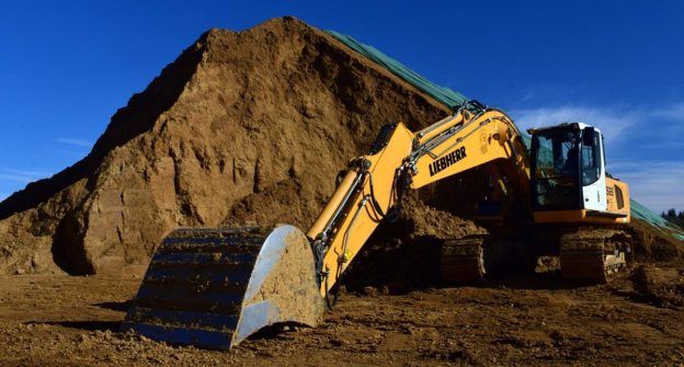 Excavator with dirt pile
