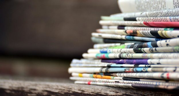 Newspapers stacked on a bench